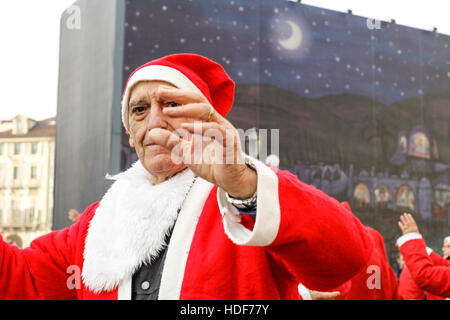 People dancing in a square with Santa Claus costumes in Italy. - Stock Photo