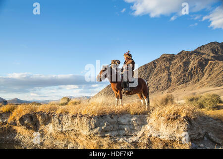 Bayan Ulgii, Mongolia, October 2nd, 2015: Old eagle hunter with his Altai Golden Eagle on his horse - Stock Photo