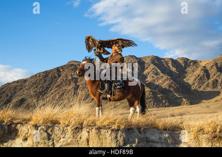 Bayan Ulgii, Mongolia, October 2nd, 2015: Old eagle hunter with his Altai Golden Eagle on his horse