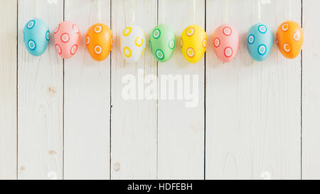 Colorful easter eggs hanging on rustic wooden white background with space. - Stock Photo