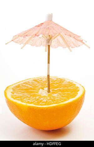 Little umbrella in a halfed orange - Stock Photo