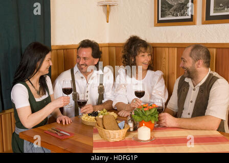 Two couples dressed in traditional clothes sitting at a table, holding up wine glasses - Stock Photo