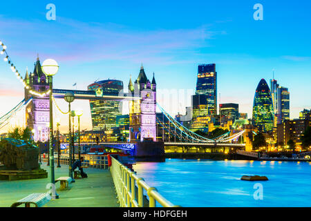 A beautiful dusk-time view of Tower Bridge and the River Thames in London, with financial district in background - Stock Photo