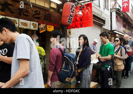 Japanese people and travelers foreigner standing queue buy takoyaki is a ball-shaped japanese snack at shop in Ameyoko - Stock Photo