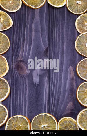 Frame from dried orange slices on dark wooden background - Stock Photo