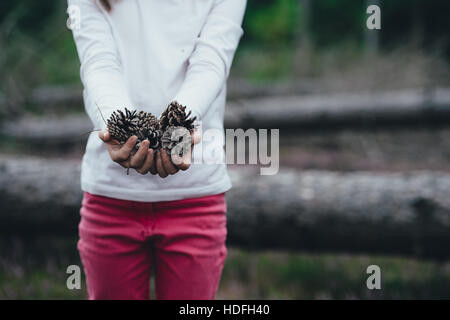 Child with pine cones in her hand. - Stock Photo