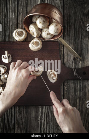 Cutting mushrooms on the wooden board vertical - Stock Photo