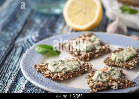 Crisp grain bread with tzatziki on the  blue ceramic plate horizontal - Stock Photo