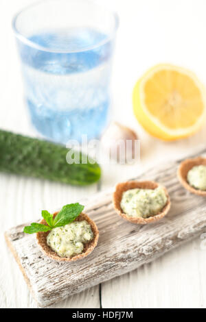 Crisp bread with tzatziki on the white wooden board vertical - Stock Photo