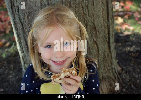 adorable school age girl eating peanut butter and jelly sandwich - Stock Photo