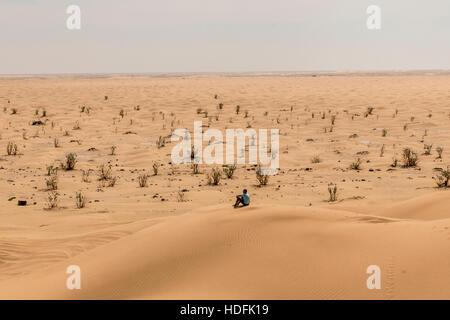 Man tourist in desert rub al khali in Oman sitting in sand view landscape - Stock Photo