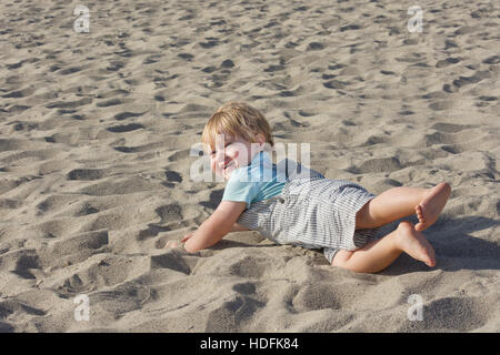 young toddler boy wearing overalls and playing on sand beach - Stock Photo