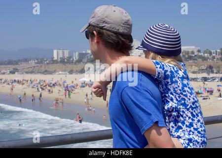 young girl riding piggy back with father on santa monica pier california - Stock Photo