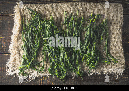 Tarragon on the canvas on the wooden table top view - Stock Photo