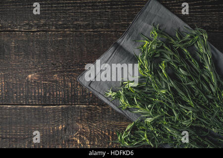 Tarragon on the grey napkin on the wooden table top view - Stock Photo