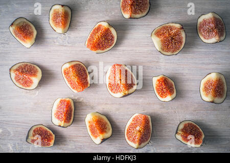 Sliced figs on the white wooden background top view - Stock Photo