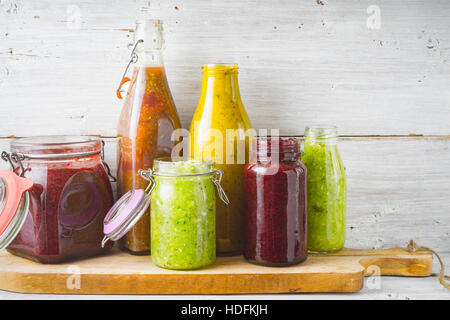 Bottles and jar with different smoothie on the  wooden board horizontal - Stock Photo