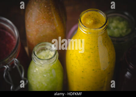 Jars and bottles with different smoothie top view - Stock Photo