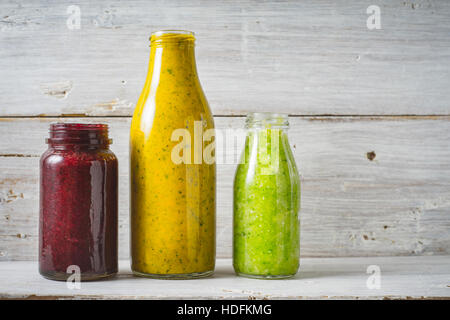 Green, yellow and red smoothie in the glass bottle on the white wooden background - Stock Photo