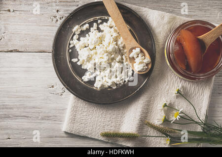 Fresh cottage cheese with  jam and flowers on the white wooden table top view - Stock Photo