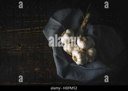 Bunch of garlic with napkin on the wooden table horizontal - Stock Photo