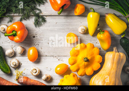 Yellow and green vegetables on the white wooden table - Stock Photo