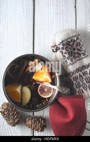 Pot with mulled whine on the white wooden table top view - Stock Photo