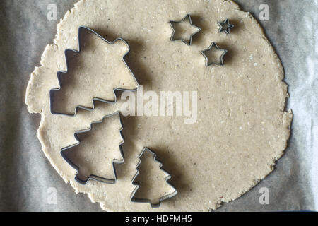 Christmas cookie cutters on the raw dough on the parchment top view - Stock Photo