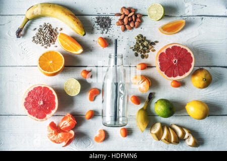 Glass bottle surrounded by different fruits and nuts on the white wooden table top view - Stock Photo