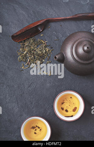 Chinese teapot and bowl  with green tea on the stone background vertical - Stock Photo