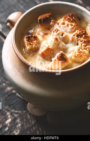 Onion soup in the ceramic pot on the  wooden table - Stock Photo