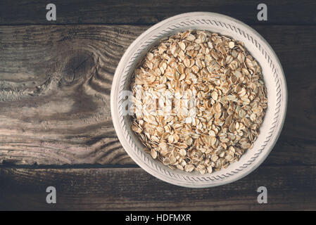 Raw oatmeal in  the bowl on the wooden table top view - Stock Photo