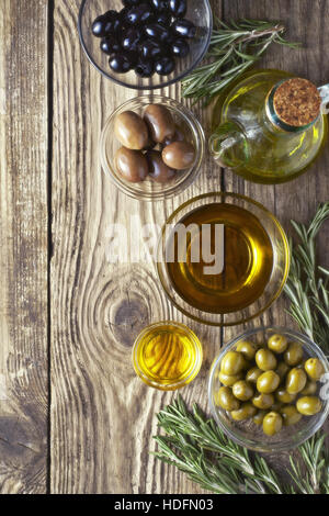 Olives with olive oil and rosemary on the wooden table