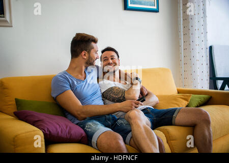 Two men in casual outfits sitting on sofa embracing and looking at each other. - Stock Photo