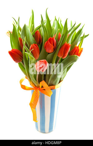Orange tulips in a blue white vase over white - Stock Photo