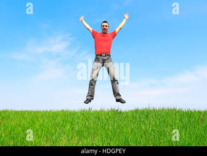Young man jump on the meadow in summer day. - Stock Photo