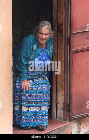 An 85 year old Mayan woman known as the Comadrona  wears traditional dress and looks out her door.  A comadrona - Stock Photo