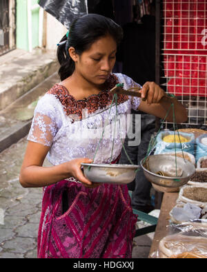 An attractive young Mayan woman in traditional dress uses a balance scale in the market at Santiago Atitlan, Guatemala. - Stock Photo