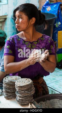 A young Mayan woman in traditional dress makes blue corn tortillas in the market at Santiago Atitlan, Guatemala. - Stock Photo