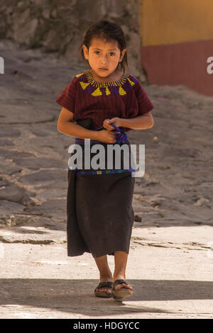 A young Mayan girl wearing traditional dress walks down the cobblestone street in the small town of Santa Cruz la - Stock Photo