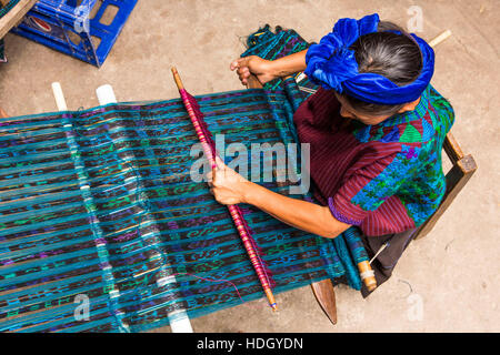 A Mayan woman in traditional dress weaves fabric on a back loom in Santa Cruz la Laguna, Guatemala.  Overhead view. - Stock Photo