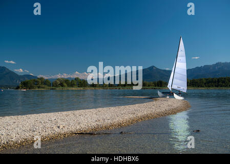 Outrigger sailboat moored on lakeshore against blue sky, Lake Chiemsee, Bavaria, Germany - Stock Photo