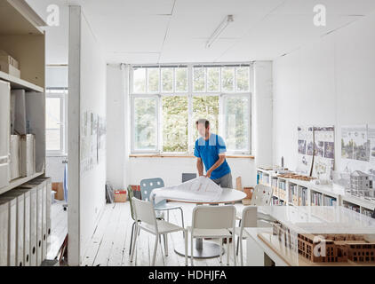 A modern office. A man looking at plans at a table, architectural drawings. Building models on shelves. Open windows. - Stock Photo