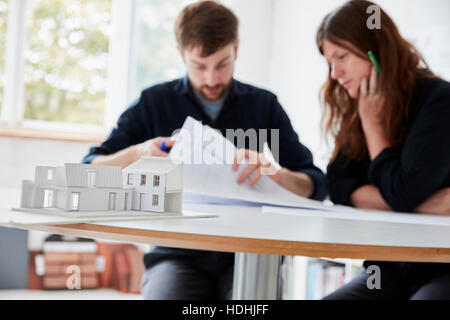 A modern office. Two people at a meeting discussing plans and architectural drawings. A small-scale model building - Stock Photo