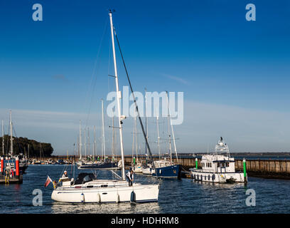 Yacht leaving harbour, Yarmouth, Isle of Wight, UK - Stock Photo