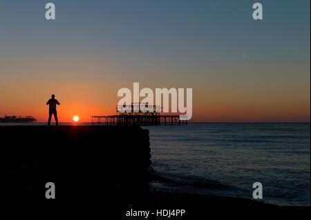 Silhouetted man standing on groyne watching sunrise between Brighton piers - Stock Photo