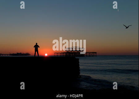 Silhouetted man standing on groyne watching sunrise between Brighton piers - Stock Photo