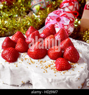 closeup of a heart-shaped cake covered with cream and topped with strawberries, on a table full of gifts and christmas - Stock Photo
