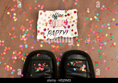 high-angle shot of the feet of a man wearing black leather shoes and a piece of paper with the text office holiday - Stock Photo