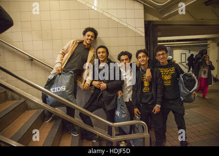 Group of teenage boys stop for a photo as they exit the 34th Street subway station during the Thanksgiving holiday - Stock Photo